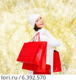 Купить «smiling young woman with red shopping bags», фото № 6392570, снято 15 августа 2013 г. (c) Syda Productions / Фотобанк Лори
