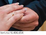 Купить «Жених надевает золотое обручальное кольцо на палец невесте», эксклюзивное фото № 6406654, снято 12 июля 2014 г. (c) Игорь Низов / Фотобанк Лори