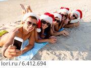 Купить «group of friends in santa hats with smartphone», фото № 6412694, снято 3 августа 2014 г. (c) Syda Productions / Фотобанк Лори