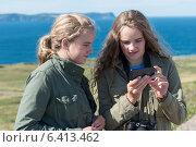 Girls looking at mobile phone on coast, Cape Spear, St. John's, Newfoundland And Labrador, Canada. Стоковое фото, агентство Ingram Publishing / Фотобанк Лори