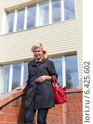 Купить «Блондинка в черном плаще с красной сумочкой на ступеньках магазина», фото № 6425602, снято 12 сентября 2014 г. (c) Евгений Ткачёв / Фотобанк Лори