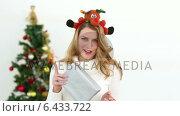 Купить «Festive blonde smiling at camera offering gift», видеоролик № 6433722, снято 18 июня 2019 г. (c) Wavebreak Media / Фотобанк Лори