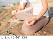 close up of couple making yoga exercises outdoors. Стоковое фото, фотограф Syda Productions / Фотобанк Лори