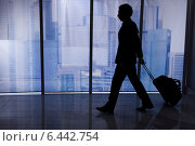 Купить «Businessman Walking With Luggage In Office», фото № 6442754, снято 6 мая 2014 г. (c) Андрей Попов / Фотобанк Лори