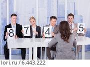 Купить «Business People Showing Score Cards In Front Of Female Candidate», фото № 6443222, снято 1 июня 2014 г. (c) Андрей Попов / Фотобанк Лори