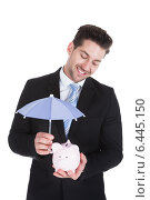 Купить «Businessman Sheltering Piggybank With Umbrella», фото № 6445150, снято 11 мая 2014 г. (c) Андрей Попов / Фотобанк Лори