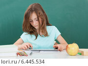 Купить «Schoolgirl Using Digital Tablet At Table», фото № 6445534, снято 14 июня 2014 г. (c) Андрей Попов / Фотобанк Лори