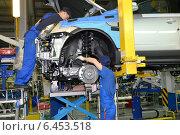 Купить «Рабочие устанавливают двигатель на легковой автомобиль. Сборочный конвейер автомобильного завода», фото № 6453518, снято 16 сентября 2014 г. (c) Ирина Борсученко / Фотобанк Лори
