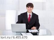 Confident Businessman With Laptop At Desk, фото № 6455670, снято 23 февраля 2014 г. (c) Андрей Попов / Фотобанк Лори