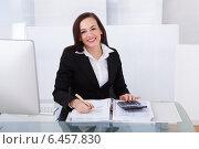 Купить «Happy Businesswoman Calculating Tax», фото № 6457830, снято 15 марта 2014 г. (c) Андрей Попов / Фотобанк Лори