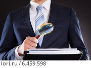 Купить «Businessman Examining Documents With Magnifying Glass», фото № 6459598, снято 10 апреля 2014 г. (c) Андрей Попов / Фотобанк Лори
