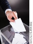 Купить «Businessman Inserting Ballot In Box On Desk», фото № 6459602, снято 10 апреля 2014 г. (c) Андрей Попов / Фотобанк Лори