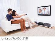Купить «Couple Watching TV In Living Room», фото № 6460318, снято 9 марта 2014 г. (c) Андрей Попов / Фотобанк Лори