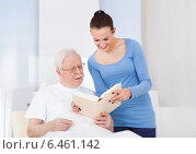 Купить «Caretaker And Senior Man Reading Book», фото № 6461142, снято 15 марта 2014 г. (c) Андрей Попов / Фотобанк Лори