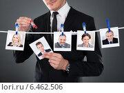 Купить «Businessman Selecting Candidate From Clothesline», фото № 6462506, снято 28 июня 2014 г. (c) Андрей Попов / Фотобанк Лори