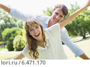 Купить «Attractive couple smiling at camera and spreading arms in the park», фото № 6471170, снято 30 января 2014 г. (c) Wavebreak Media / Фотобанк Лори