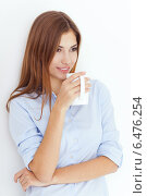 Девушка в светло-голубой рубашке держит чашку чая или кофе. Стоковое фото, фотограф Viktor Gladkov / Фотобанк Лори