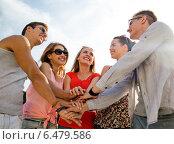 Купить «group of smiling friends with hands on top in city», фото № 6479586, снято 20 июля 2014 г. (c) Syda Productions / Фотобанк Лори