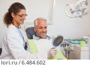Купить «Dentist showing patient his new smile in the mirror», фото № 6484602, снято 15 апреля 2014 г. (c) Wavebreak Media / Фотобанк Лори