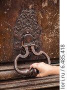 Рука тянет за старую дверную ручку-молоток на коричневой деревянной двери. Париж, Франция. Стоковое фото, фотограф EugeneSergeev / Фотобанк Лори