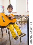 Купить «Cute pupil playing guitar in classroom», фото № 6500154, снято 11 мая 2014 г. (c) Wavebreak Media / Фотобанк Лори