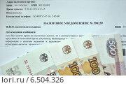Купить «Фрагмент налогового уведомления и деньги», фото № 6504326, снято 4 октября 2014 г. (c) Николай Белецкий / Фотобанк Лори