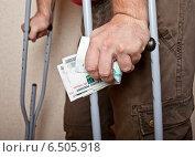Купить «Мужские руки на костылях с деньгами на фоне стены», фото № 6505918, снято 8 октября 2014 г. (c) Элина Гаревская / Фотобанк Лори