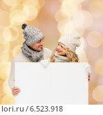 Купить «smiling couple in winter clothes with white board», фото № 6523918, снято 7 октября 2012 г. (c) Syda Productions / Фотобанк Лори