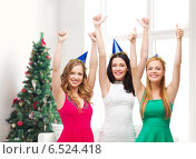 Купить «smiling women in party caps showing thumbs up», фото № 6524418, снято 20 октября 2013 г. (c) Syda Productions / Фотобанк Лори