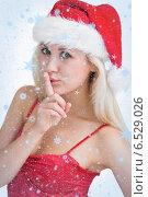 Woman in santa hat making silence gesture. Стоковое фото, агентство Wavebreak Media / Фотобанк Лори