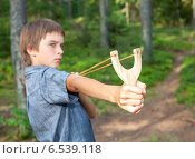 Купить «Мальчик стреляет из рогатки», фото № 6539118, снято 30 июля 2014 г. (c) Дмитрий Наумов / Фотобанк Лори