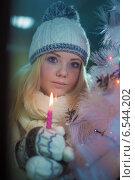 Девушка в шапочке стоит у окна с горящей свечой. Стоковое фото, фотограф Юрий Викулин / Фотобанк Лори