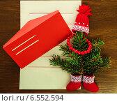 Новогоднее письмо с красным конвертом и зеленой елкой, украшенной красными бусами, вязаной шапочкой и валенками с кружевом на деревянном фоне. Стоковое фото, фотограф Marina Kutukova / Фотобанк Лори