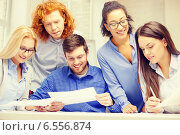 Купить «smiling team with paper at office», фото № 6556874, снято 1 февраля 2014 г. (c) Syda Productions / Фотобанк Лори
