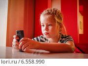 Купить «Девочка смотрит в телефон», фото № 6558990, снято 11 октября 2014 г. (c) Хайрятдинов Ринат / Фотобанк Лори