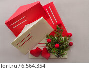 Новогодняя открытка- письма Санта Клаусу с листами бумаги, красными и желтыми конвертами, елочки с бусинами и красными валенками на льняной салфетке. Стоковое фото, фотограф Marina Kutukova / Фотобанк Лори
