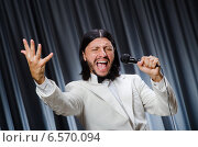 Man singing in front of curtain in karaoke concept. Стоковое фото, фотограф Elnur / Фотобанк Лори