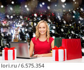 Купить «smiling woman in red shirt with gifts and laptop», фото № 6575354, снято 27 сентября 2013 г. (c) Syda Productions / Фотобанк Лори