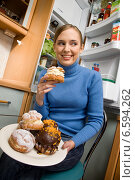 A woman holding a plate with donuts and cream puffs and eating a cream puff. Стоковое фото, агентство BE&W Photo / Фотобанк Лори