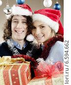 Купить «Portrait of a young woman and a man with presents, wearing Christmas caps.», фото № 6594662, снято 13 июля 2020 г. (c) BE&W Photo / Фотобанк Лори