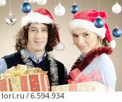 Купить «Portrait of a young woman and a man with presents, wearing Christmas caps.», фото № 6594934, снято 15 ноября 2018 г. (c) BE&W Photo / Фотобанк Лори