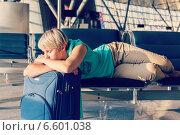 Купить «Девушка с чемоданом лежит на сидениях в аэропорту в ожидании рейса», фото № 6601038, снято 17 июля 2018 г. (c) Mikhail Starodubov / Фотобанк Лори