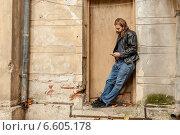 Длинноволосый и бородатый мужчина-хипстер в кожаной куртке слушает музыку, прислонившись к стене здания (2014 год). Стоковое фото, фотограф Ilie-Cristian IONESCU / Фотобанк Лори