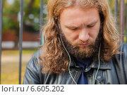 Молодой длинноволосый мужчина с бородой в черной кожаной куртке слушает музыку в наушниках (2014 год). Стоковое фото, фотограф Ilie-Cristian IONESCU / Фотобанк Лори