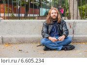 Длинноволосый бородатый мужчина в кожаной куртке слушает музыку в парке в наушниках, сидя на асфальте (2014 год). Стоковое фото, фотограф Ilie-Cristian IONESCU / Фотобанк Лори