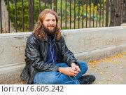 Бородатый мужчина с длинными волосами в черной кожаной куртке слушает музыку в парке в наушниках, сидя на асфальте около забора (2014 год). Стоковое фото, фотограф Ilie-Cristian IONESCU / Фотобанк Лори