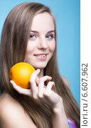 Красивая девушка с апельсином на голубом фоне. Стоковое фото, фотограф Nikolay Safronov / Фотобанк Лори