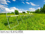 Купить «Пять складных стульев стоят в ряд на зеленой траве», фото № 6612858, снято 8 июня 2014 г. (c) Сергей Новиков / Фотобанк Лори