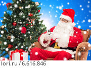 santa claus with smartphone and christmas tree. Стоковое фото, фотограф Syda Productions / Фотобанк Лори