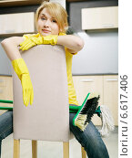 Купить «A tired woman wearing plastic gloves sitting on a chair in the kitchen with a broom and a mop.», фото № 6617406, снято 15 декабря 2018 г. (c) BE&W Photo / Фотобанк Лори